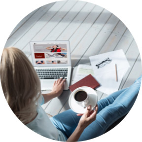 Barefoot woman in jeans looking at laptop and papers with a cup of coffee