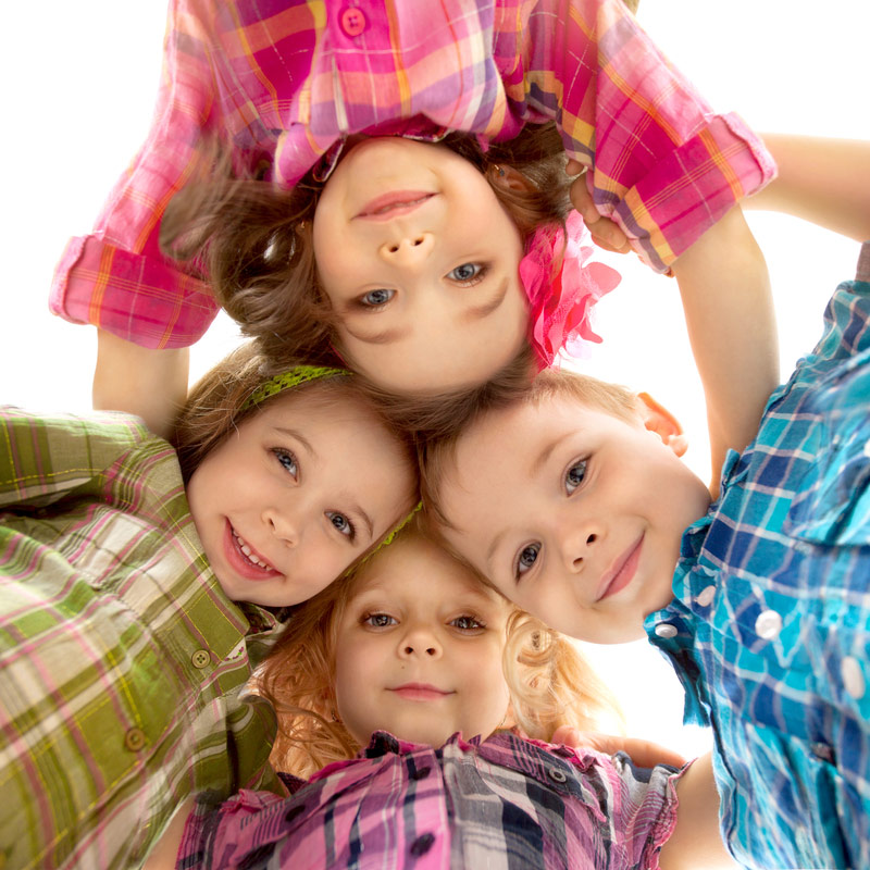 Smiling kids in a huddle, all wearing plaid shirts